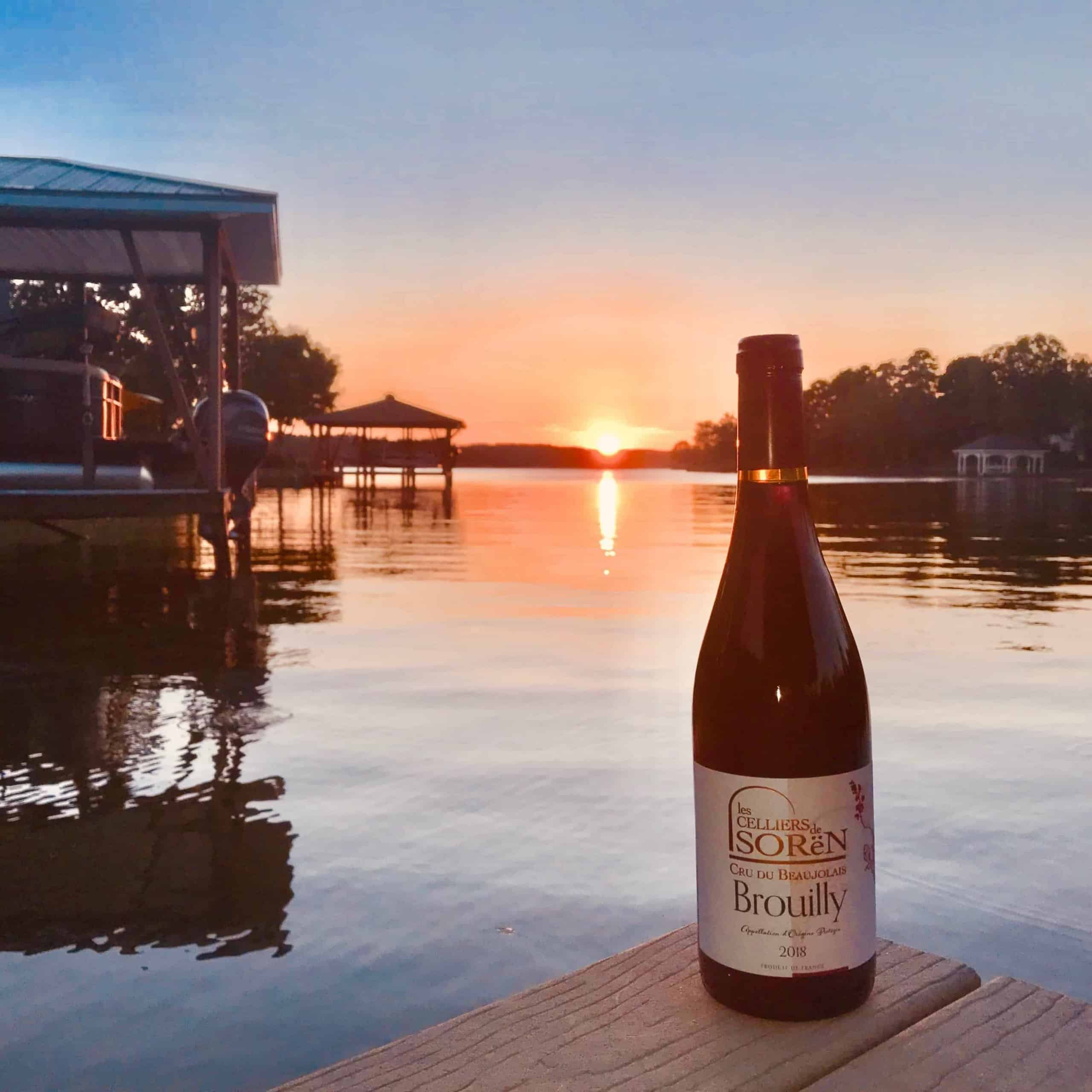An image of Les Celliers de Sorén Beaujolais wine lakeside at sunset